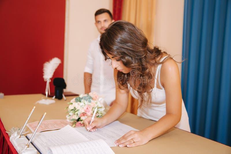 Situaci?n del novio y de la novia dentro de la casa del matrimonio Pares hermosos en blanco imagen de archivo