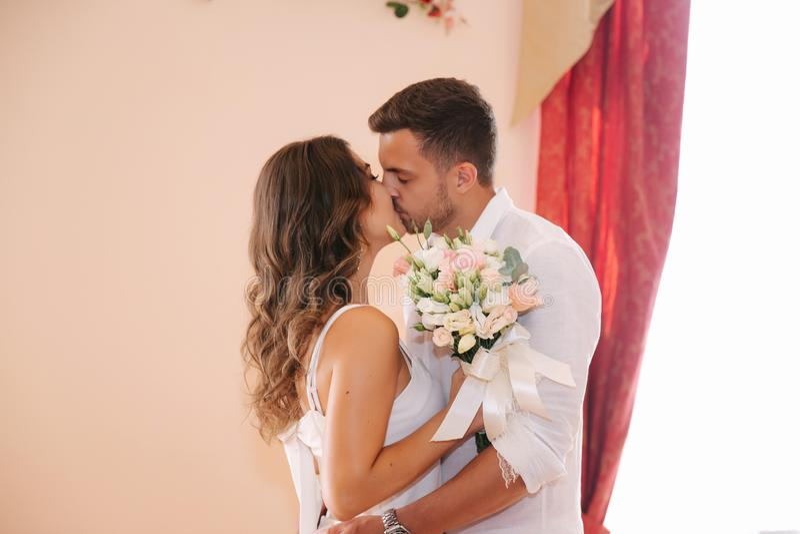 Situaci?n del novio y de la novia dentro de la casa del matrimonio Pares hermosos en blanco foto de archivo