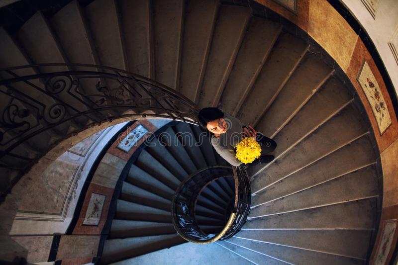 Situaci?n hermosa joven de la mujer en escalera espiral redonda vieja Visi?n superior fotos de archivo