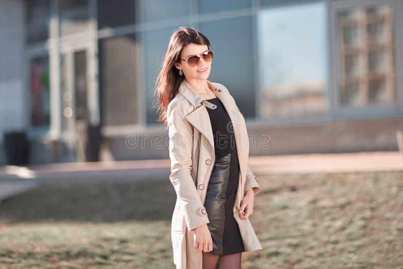 Situaci?n joven de la mujer de negocios en la calle cerca del edificio de oficinas fotografía de archivo