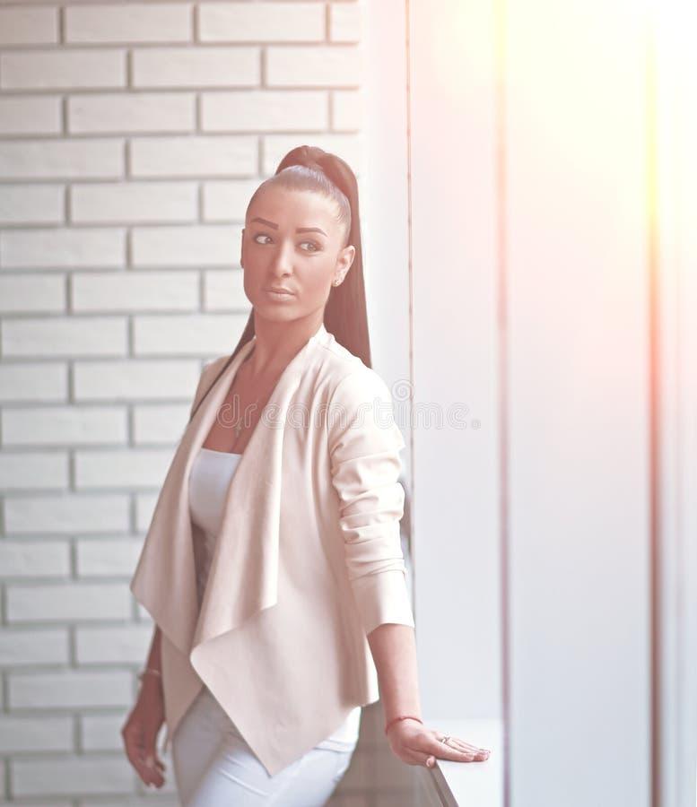 Situaci?n moderna de la mujer de negocios cerca de la ventana en el pasillo imagen de archivo