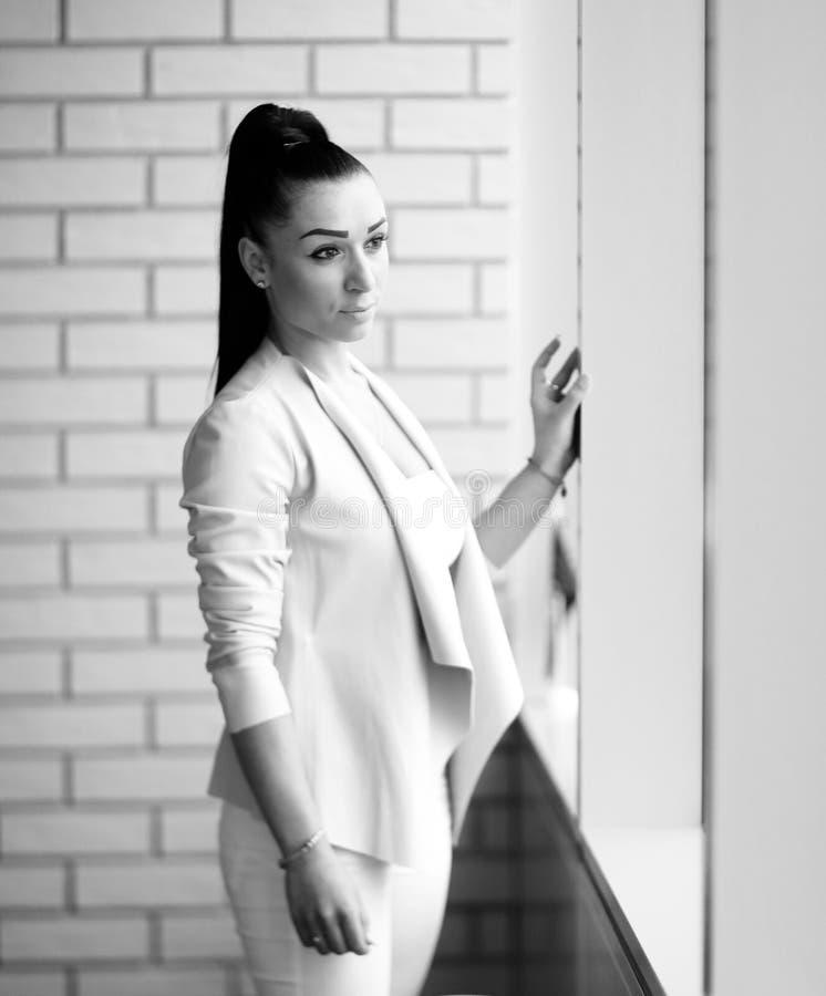 Situaci?n moderna de la mujer de negocios cerca de la ventana en el pasillo foto de archivo libre de regalías