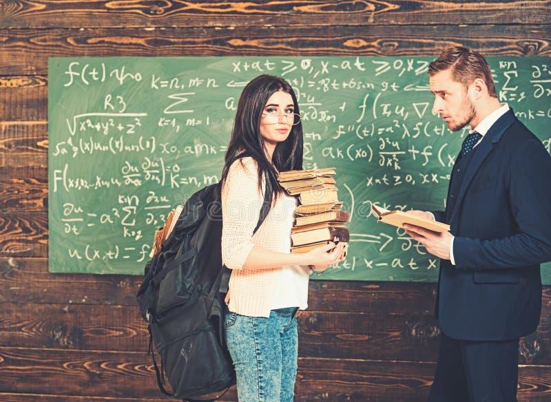 Situaci?n morena del estudiante delante del tablero verde con el mont?n de libros y de la mochila enorme Profesor que mira imagen de archivo libre de regalías