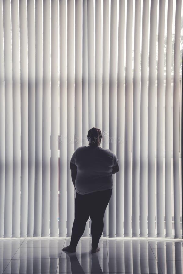 Situaci?n obesa sola de la mujer cerca de la ventana imagen de archivo libre de regalías