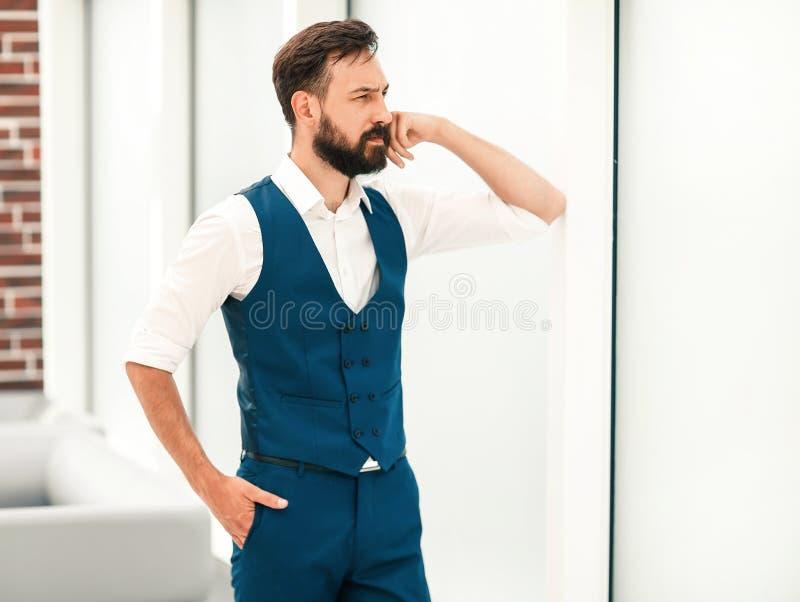 situaci?n pensativa del hombre de negocios cerca de la ventana de la oficina imagen de archivo