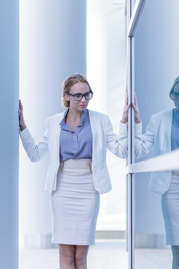 Situaci?n subrayada de la mujer de negocios al lado de la pared de un edificio de oficinas foto de archivo