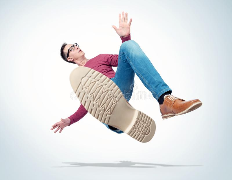 Situation, the man in casual clothes and glasses is falling down. Concept of an accident stock image