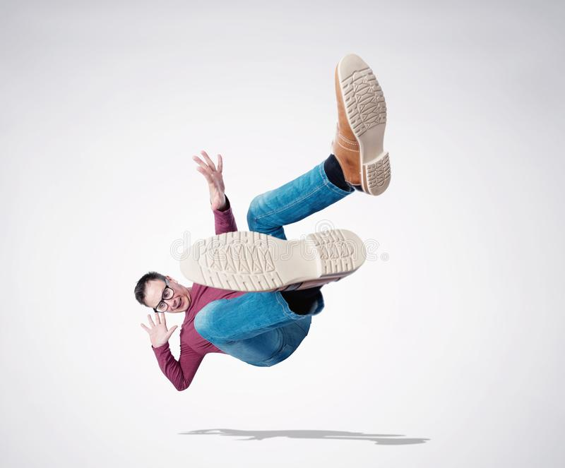 Situation, the man in casual clothes and glasses is falling down. Concept of an accident stock images