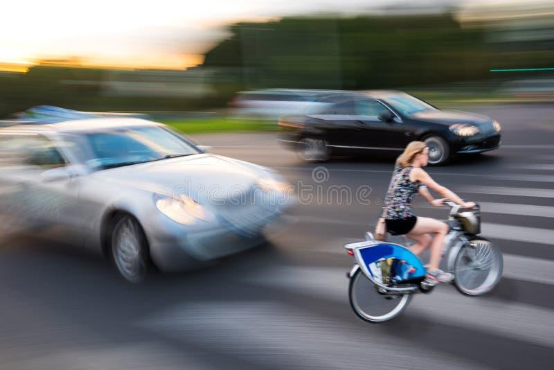 Situazione pericolosa del traffico cittadino con il ciclista e l'automobile nella CIT immagine stock libera da diritti