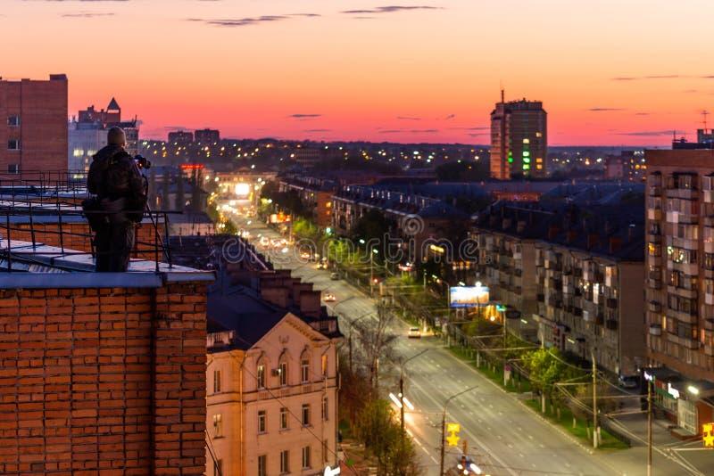 Sity da noite do tiro do fotógrafo da borda do telhado do condomínio do tijolo vermelho fotografia de stock royalty free