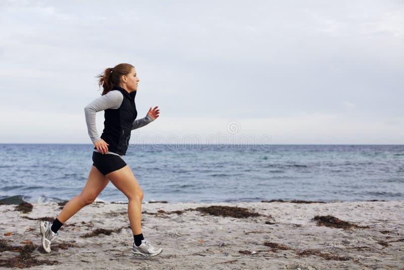 Sitz und gesunde junge Frau, die entlang Küstenlinie laufen lizenzfreie stockbilder