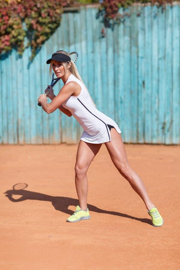 Sitz, wellenartig bewegender Schläger des sexy Mädchens auf einem Badmintonstadionshintergrund Sommer trägt Konzept zur Schau Kop stockfotos