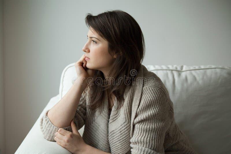Sitzen auf dem Sofa und Denken lizenzfreie stockbilder