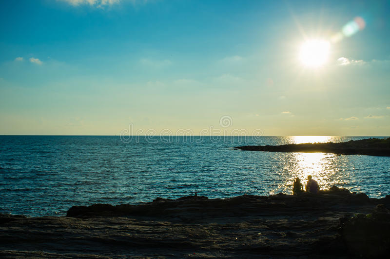 Sitzen auf den Felsen mit Sun, der -2 hinuntergeht lizenzfreies stockfoto