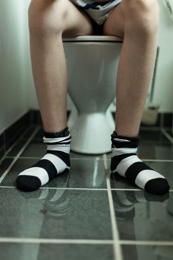 Sitzen auf einer Toilette lizenzfreie stockbilder