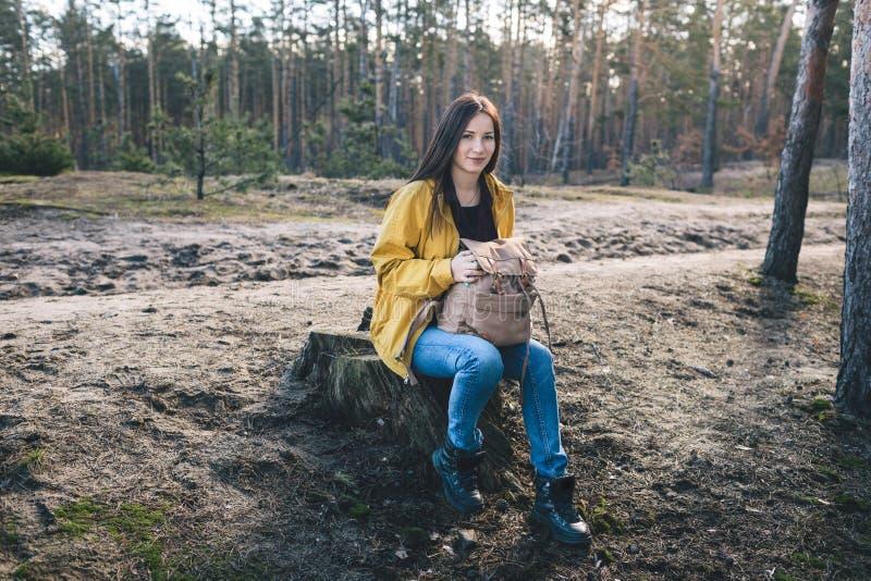 Sitzen der jungen Frau, das auf dem Waldrasen Reiselebensstil stillsteht stockfotografie