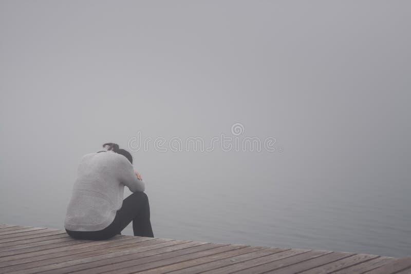 Sitzen der jungen Frau einsam am Rand eines Weges verbogen und mit ihrem Kopf in ihren Armen traurig sich verstecken lizenzfreie stockbilder
