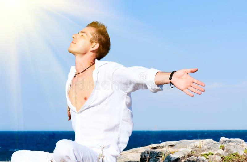 Sitzen des gutaussehenden Mannes im Freien nahe dem Meer mit den offenen Armen stockfotografie