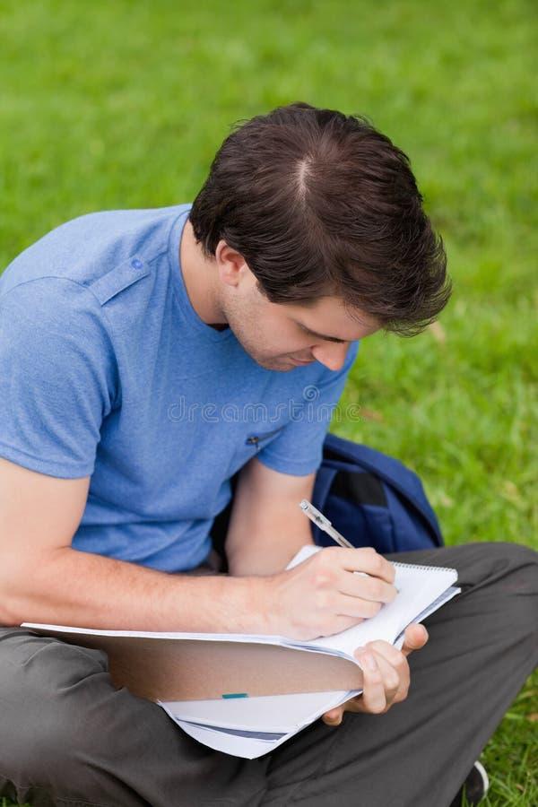 Sitzen des jungen Mannes beim Schreiben auf sein Notizbuch stockbilder