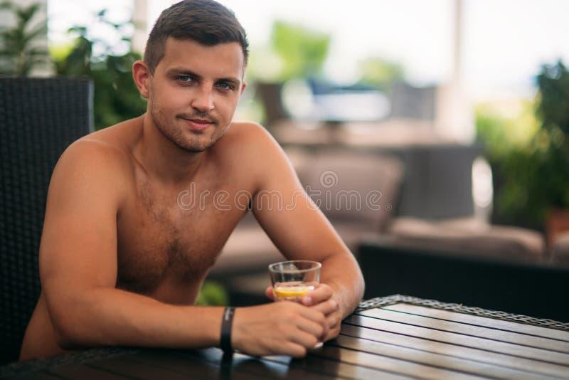 Sitzen des jungen Mannes der Strandclubbar und des trinkenden Stärkungsmittels stockfoto