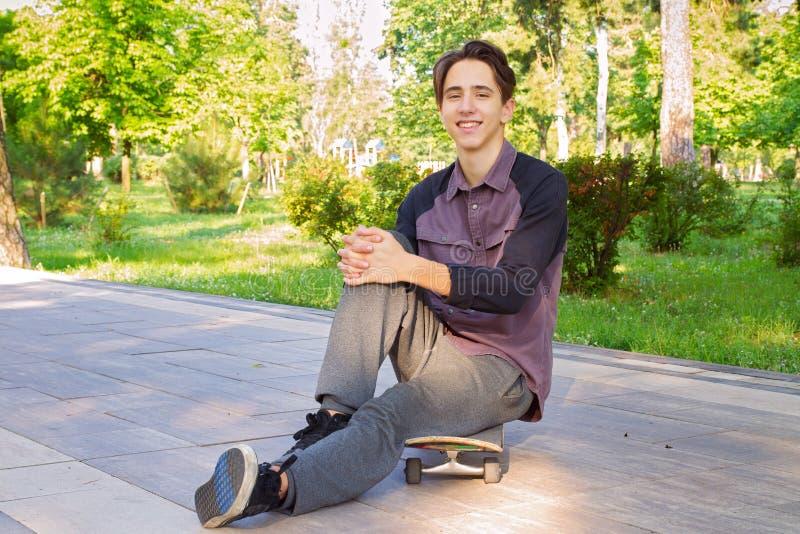 Sitzen des jungen Mannes und Entspannung auf Skateboard nach dem Eislauf in Stadtpark Jugendlich Jungenschlittschuhläufer lizenzfreie stockfotografie