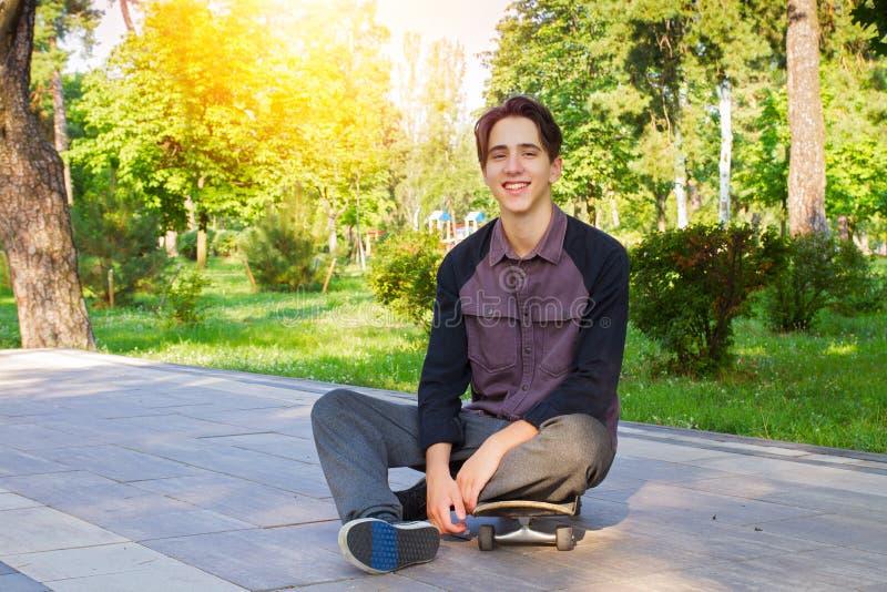 Sitzen des jungen Mannes und Entspannung auf Skateboard nach dem Eislauf in Stadtpark Jugendlich Jungenschlittschuhläufer lizenzfreie stockbilder
