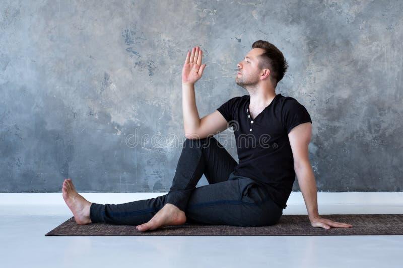 Sitzen des jungen Mannes verdreht auf dem Boden, zurück ausdehnend, Seitenansicht stockbilder
