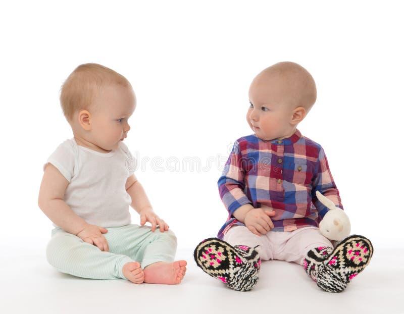 Sitzen mit zwei Kinderbaby-Kleinkindern stockfoto
