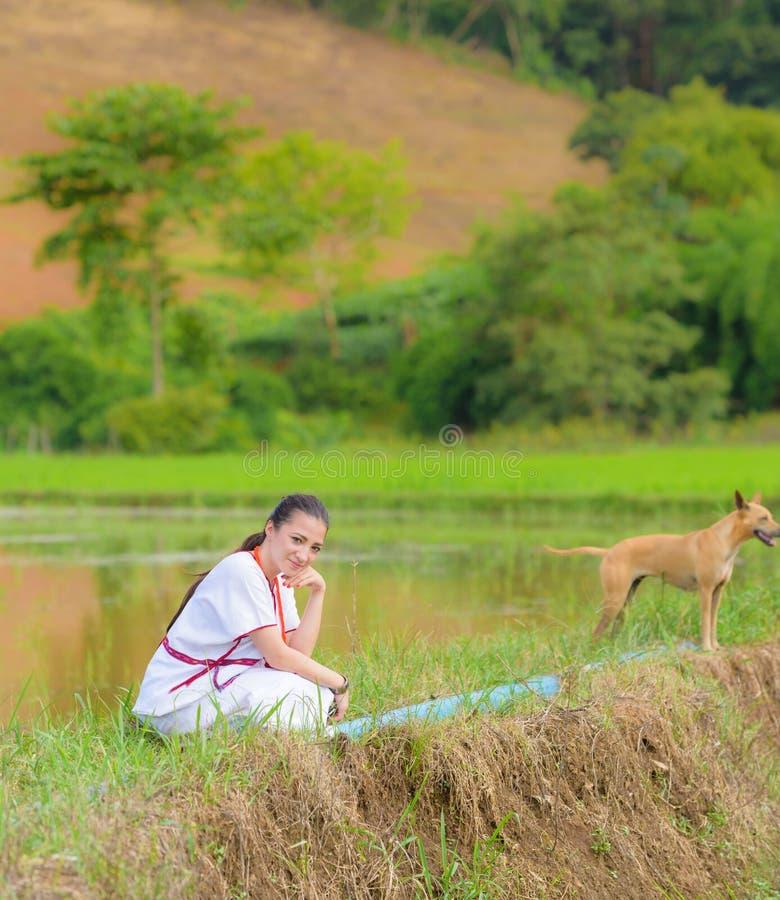 Sitzen schönes Karen-Mädchen der Mischrasse auf Reisfeld lizenzfreie stockbilder