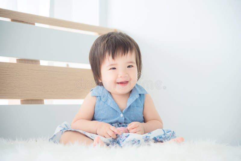 Sitzen und Lächeln des kleinen Mädchens auf Bett im Schlafzimmer stockfoto