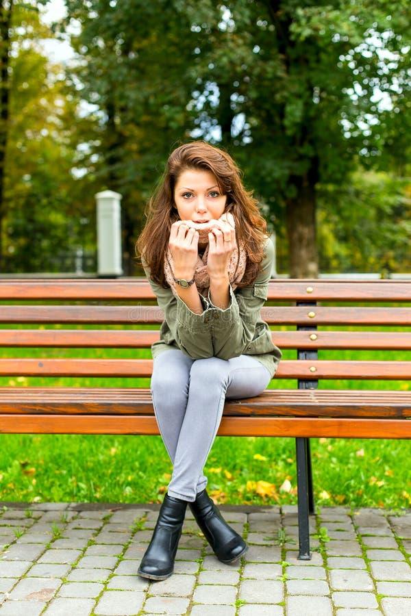 Sitzende Bank der Frau draußen lizenzfreie stockfotografie