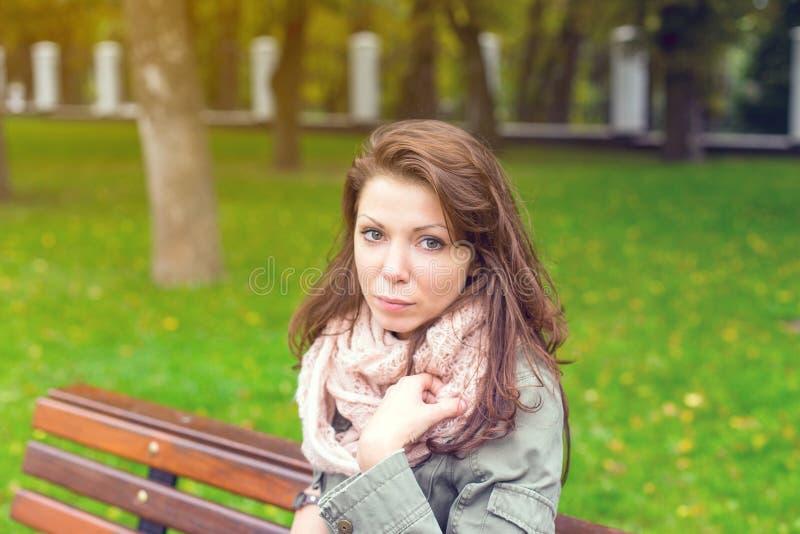 Sitzende Bank der Frau draußen stockfoto