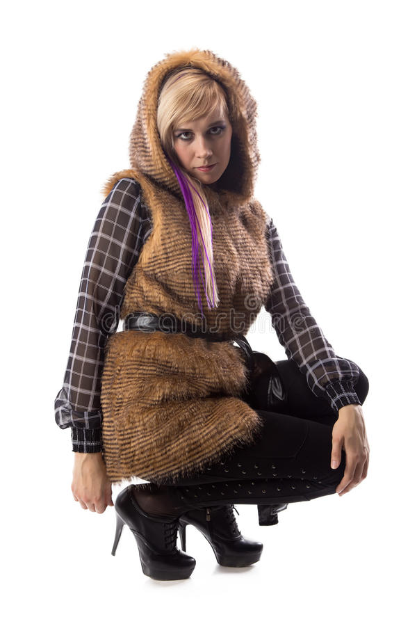 Sitzende Blondine in der braunen Pelzjacke mit Haube lizenzfreie stockbilder