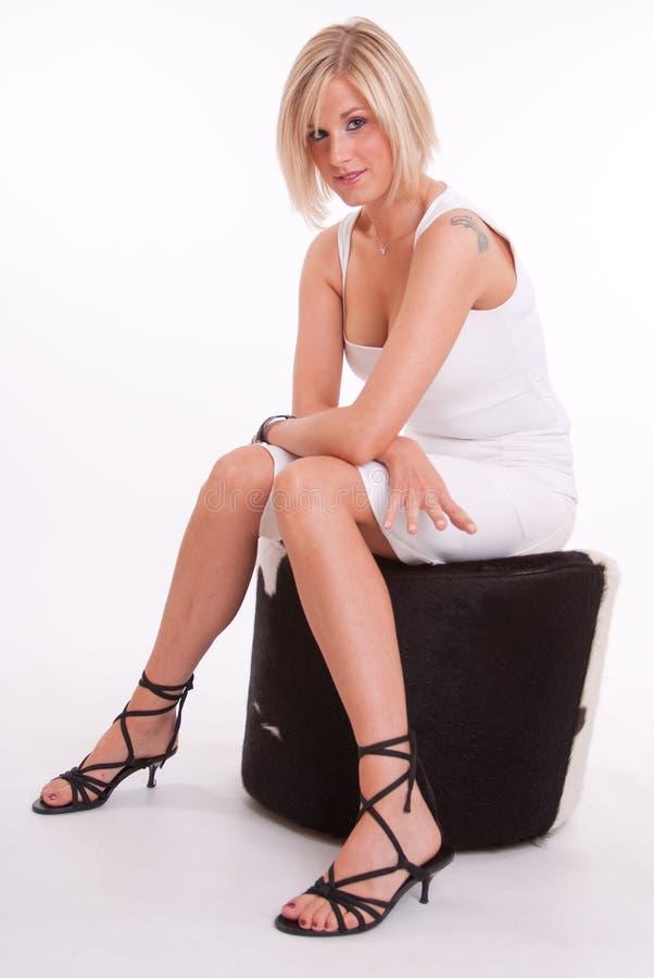 Sitzende Blondine mit Tätowierung stockfotografie