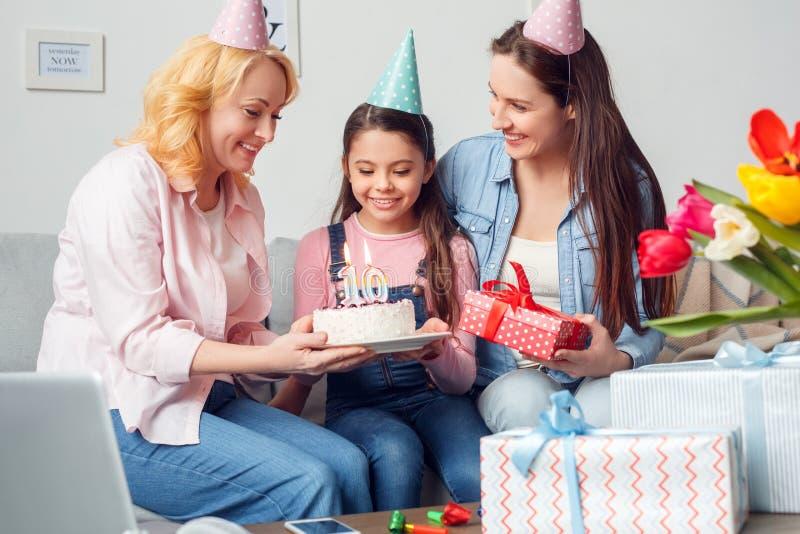 Sitzende Frauen des Großmuttermutter- und -tochterzusammen zu Hause Geburtstages, die dem Mädchen Kuchen und Geschenk froh geben stockfotos