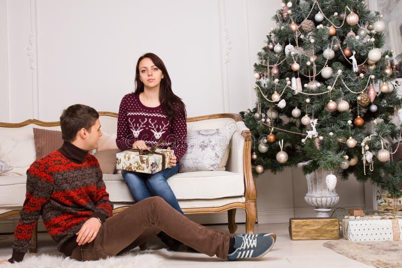Sitzende junge Paare nähern sich Weihnachtsbaum stockfotografie
