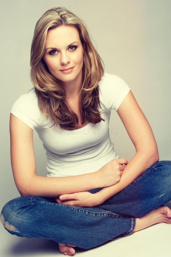 Sitzende lächelnde Frau stockbilder