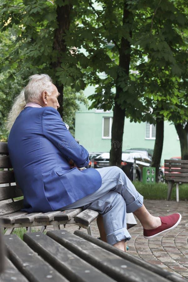 Sitzende Leute, moderne Kleidung, Parkbank in einer modernen Verdichtereintrittslufttemperat stockfoto