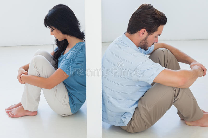 Sitzende Paare werden durch weiße Wand getrennt stockfotografie