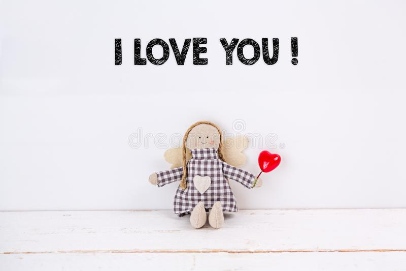 Sitzende Puppe der Marionette mit einem roten Herzen und einem Text ?ich liebe dich ?auf einem wei?en Hintergrund lizenzfreies stockfoto