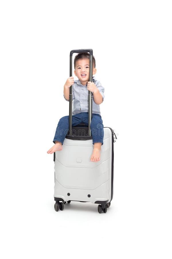 Sitzende Reisetasche oder -koffer des glücklichen asiatischen Babys lokalisiert auf weißem Hintergrund, lizenzfreies stockbild