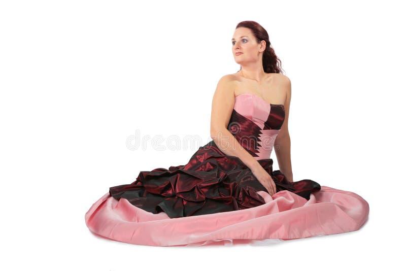 Sitzende schöne Frau im luxuriösen Kleid lizenzfreies stockbild