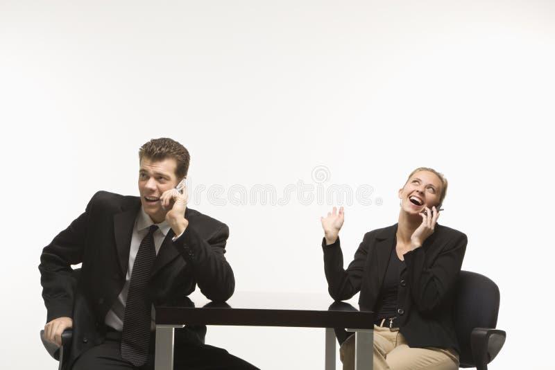 Sitzende Unterhaltung des Geschäftsmannes und der Frau auf Handys. stockbilder
