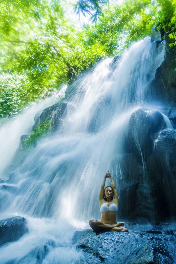 Sitzende Yogahaltung der Frau in der geistiger Entspannungsruhe und -meditation an erstaunlichem schönem Wasserfall- und Regenwal stockfoto