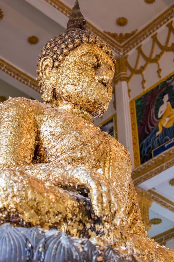 Sitzender Buddha vergoldet von den Blumenblättern stockfoto