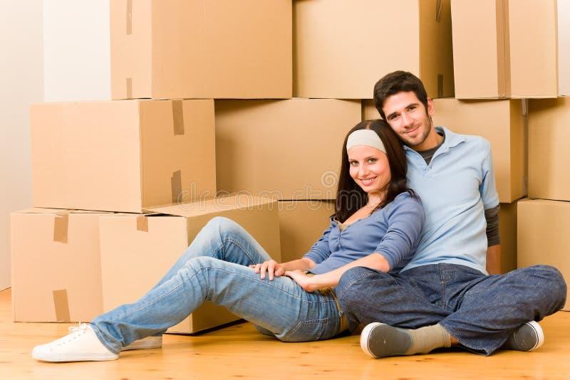 Sitzender Fußboden der beweglichen neuen jungen Hauptpaare lizenzfreie stockbilder