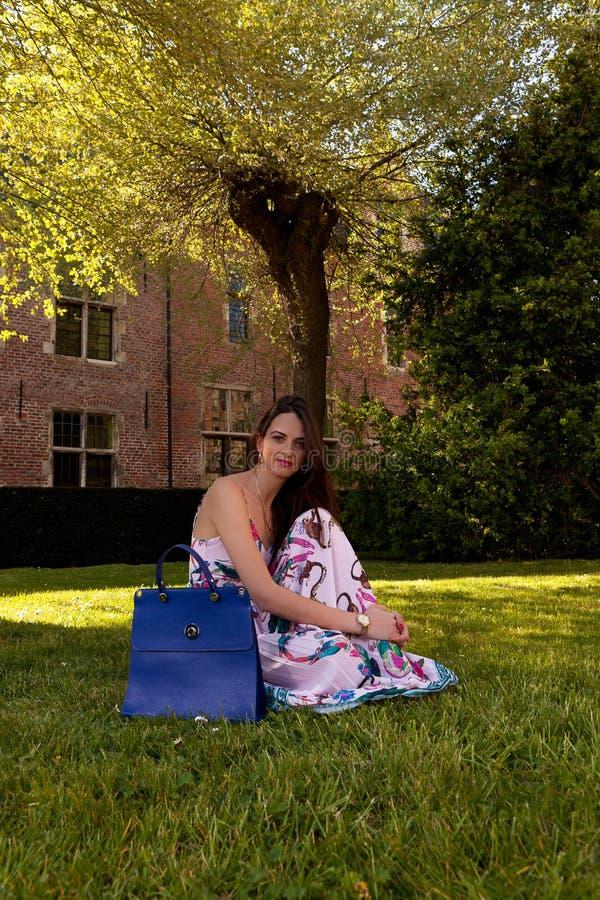 Sitzender Grasbaum des entspannten Mädchens, Groot Begijnhof, Löwen, Belgien lizenzfreie stockfotografie