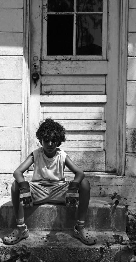 Sitzender Junge auf Jobstepps stockbild