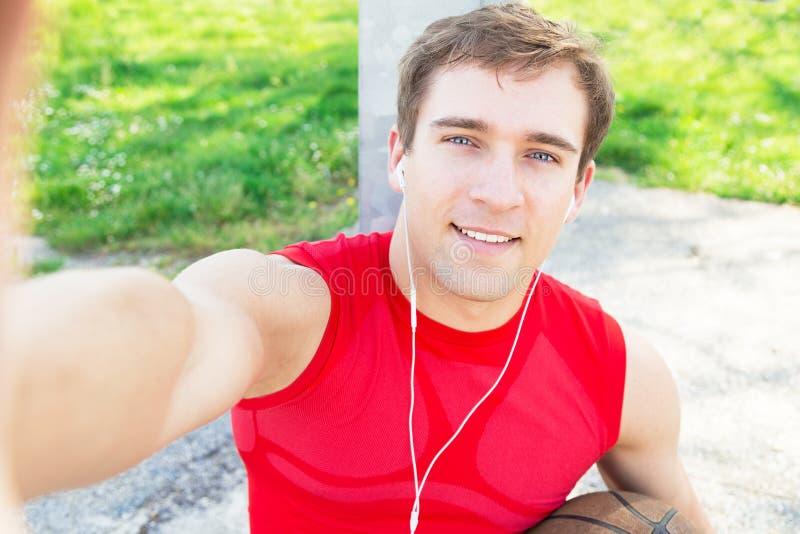 Sitzender Kerl in einem Basketballplatz und nehmen ein selfie nachdem Match mit Freunden - hört Musik mit Kopfhörern lizenzfreies stockfoto