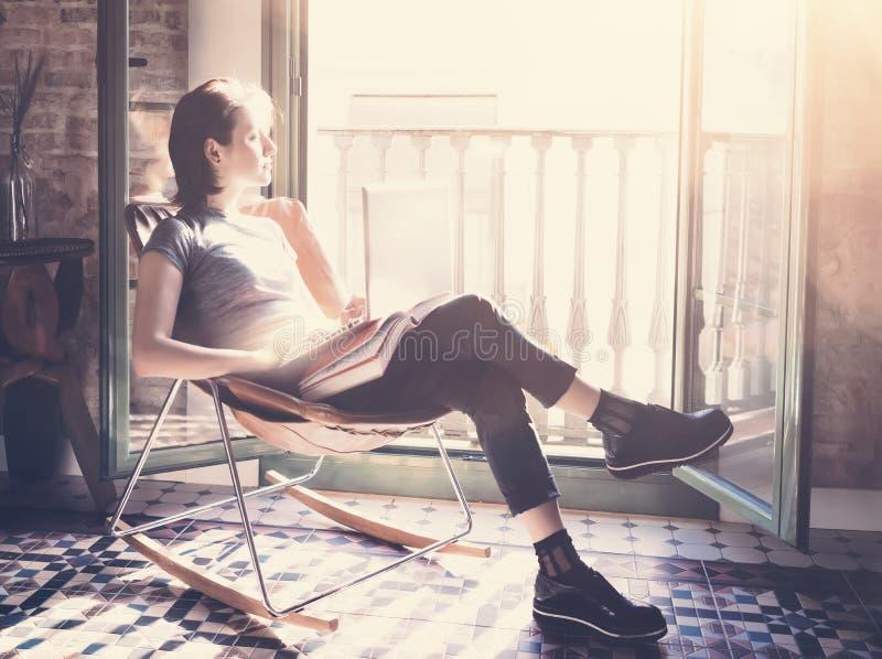 Sitzender Ledersessel des jungen Mädchens im modernen Internet des Gebäude- und Gebrauchslaptopradioapparates Studieren an der Un stockfotografie